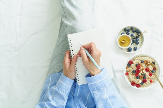 De vrouw schrijft in groot wit open notitieboekje, op bed ligt