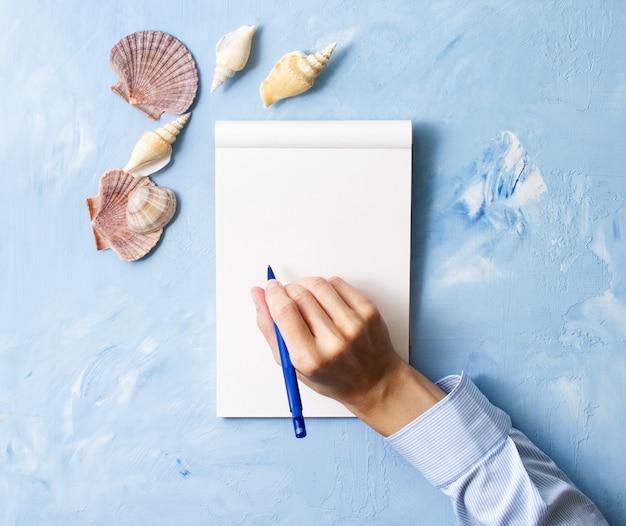De vrouw schrijft in notitieboekje op steen blauwe lijst, bespot omhoog met kader van zeeschelp