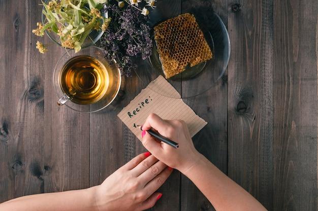 De vrouw schrijft recept van geneeskrachtige kruidenom lijst
