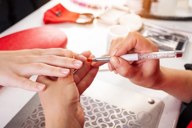 De vrouw smeert de nagels van de klant in met een borstel.
