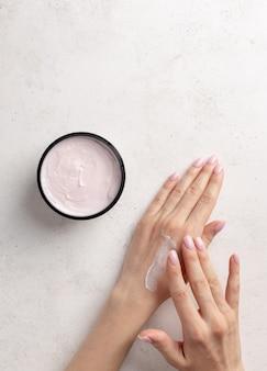 De vrouw smeert handen bevochtigende room witte steen van het achtergrondhuidzorg het exemplaarruimte concept