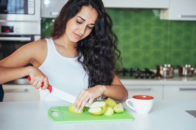 De vrouw sneed groenten samen in de keuken.