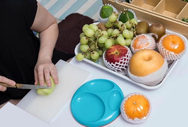 De vrouw sneed kiwi, druiven, appelen, avocado, chinese peer, sinaasappel door mes