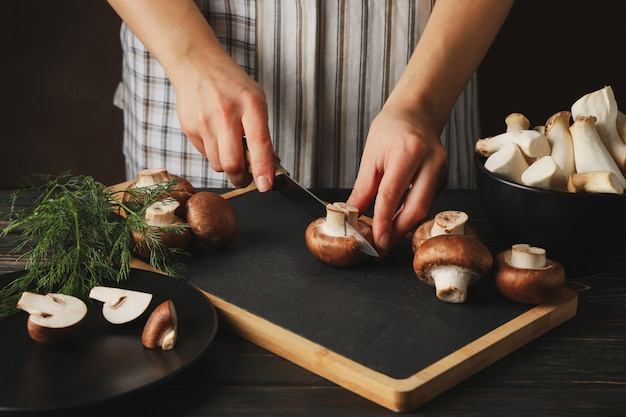 De vrouw snijdt champignon op scherpe raad met paddestoelen, omhoog sluit