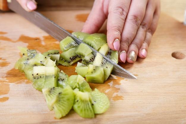 De vrouw snijdt in kleine stukjes een mes-kiwi op een snijplank