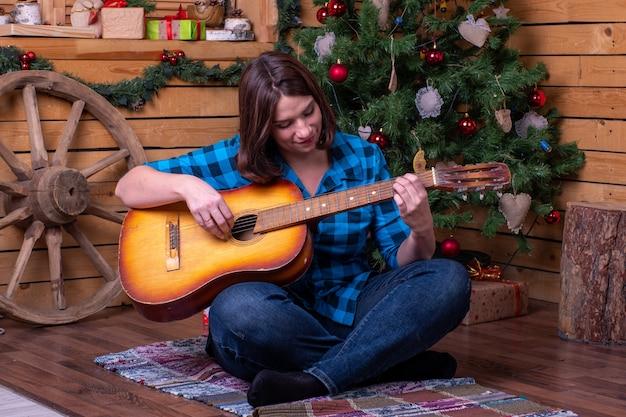De vrouw speelt gitaar tegen de achtergrond van de kerstboom