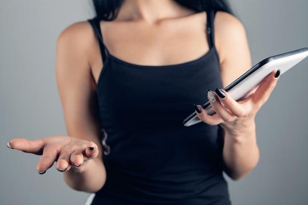 De vrouw spreidde verrast haar armen terwijl ze de tablet vasthield
