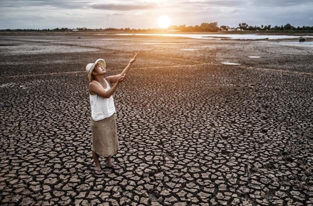 De vrouw staat naar de lucht te kijken en vroeg om regen bij droog weer, opwarming van de aarde