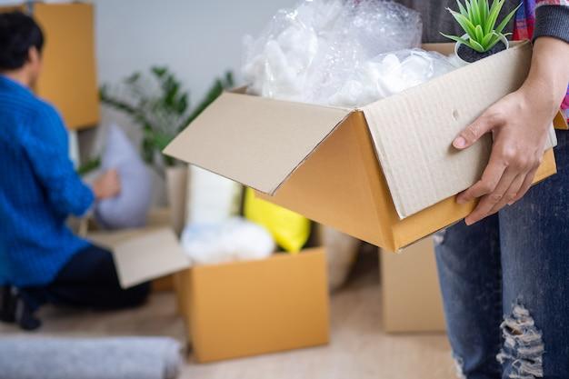 De vrouw tilde de opbergdoos op. koppels helpen elkaar om hun bezittingen te bewaren en naar een nieuw huis te verhuizen.