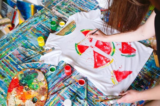 De vrouw trekt watermeloenplakken op een wit t-shirt