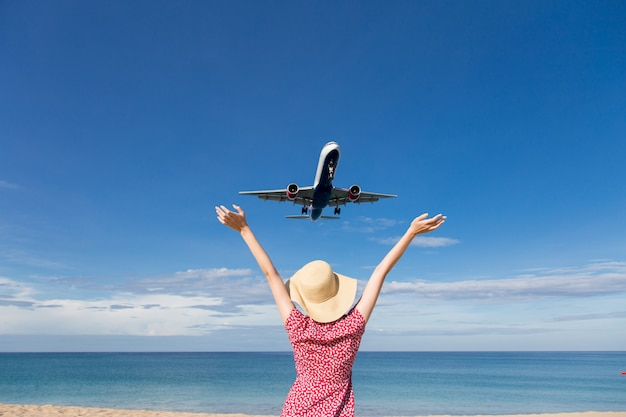 De vrouw van azië het reizen ontspant vakantievakantie en bekijkt het vliegende vliegtuig boven het overzees