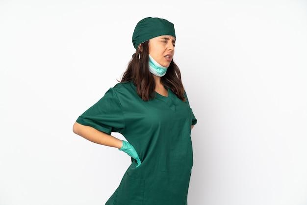 De vrouw van de chirurg in groen uniform die op witte muur wordt geïsoleerd die aan rugpijn lijdt voor het hebben van een inspanning