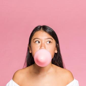 De vrouw van de close-up blaast een roze ballon op