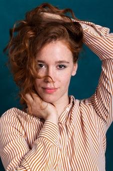 De vrouw van de close-up het stellen met gestreept chemise