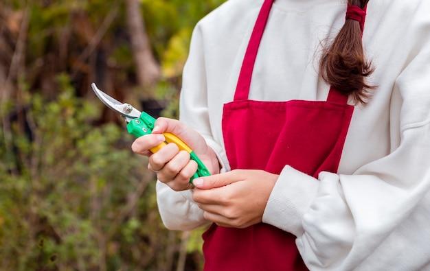 De vrouw van de close-up kleedde zich in het tuinieren kleren houdend snoeischaar