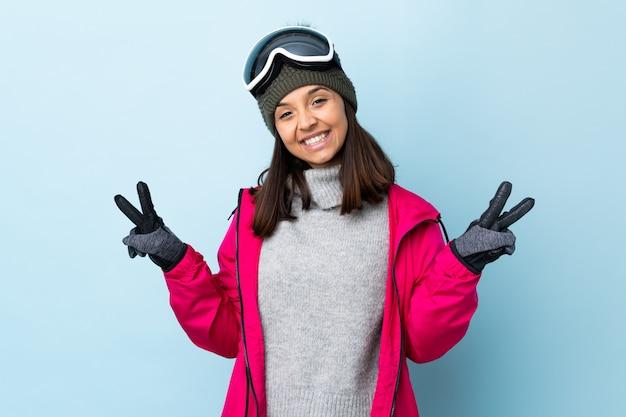 De vrouw van de gemengde rasskiër met snowboarding glazen over geïsoleerde blauwe ruimte die overwinningsteken met beide handen toont
