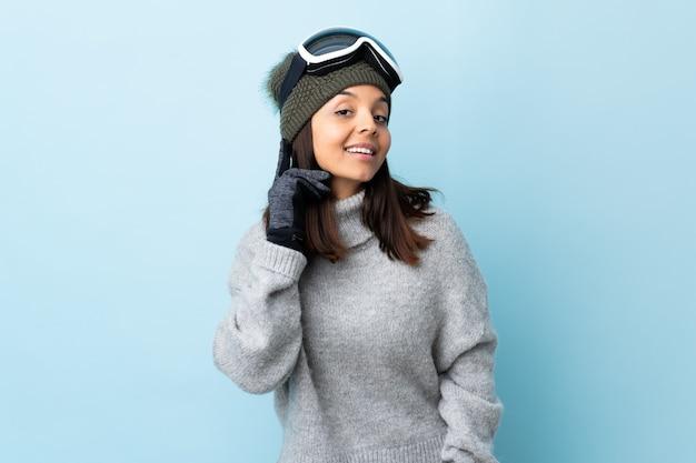 De vrouw van de gemengde rasskiër met snowboarding glazen over het geïsoleerde blauwe ruimte lachen