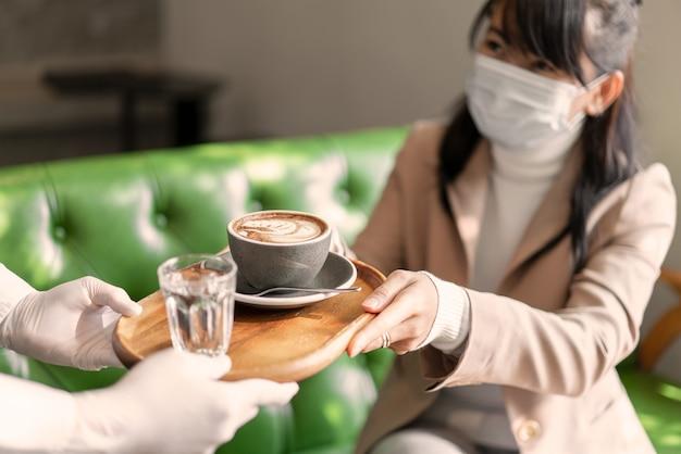 De vrouw van de hand neemt hete koffie van serveerster in coffeeshop