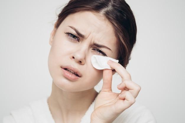 De vrouw van de huidzorg veegt haar gezicht af met een witte spons. hoge kwaliteit foto