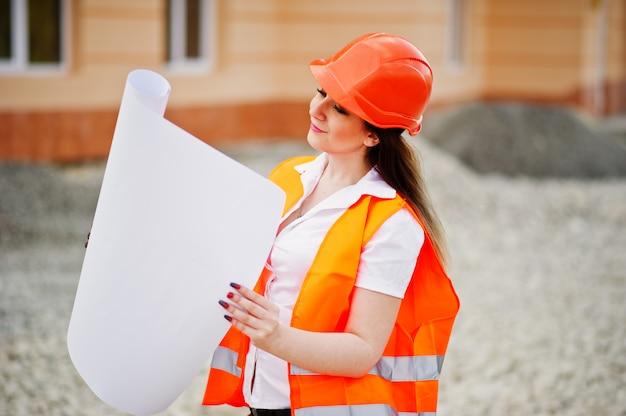 De vrouw van de ingenieursbouwer in eenvormig vest en oranje beschermend helm houdt handelspapier tegen de nieuwe bouw