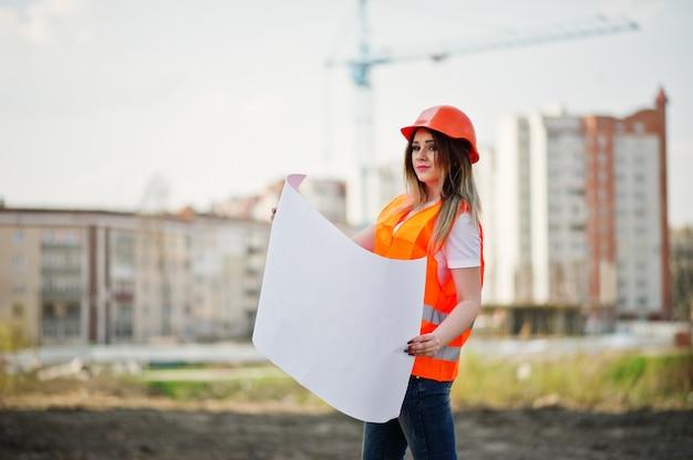 De vrouw van de ingenieursbouwer in eenvormig vest en oranje beschermende helm houdt handelspapier tegen nieuwe gebouwen met kraan.