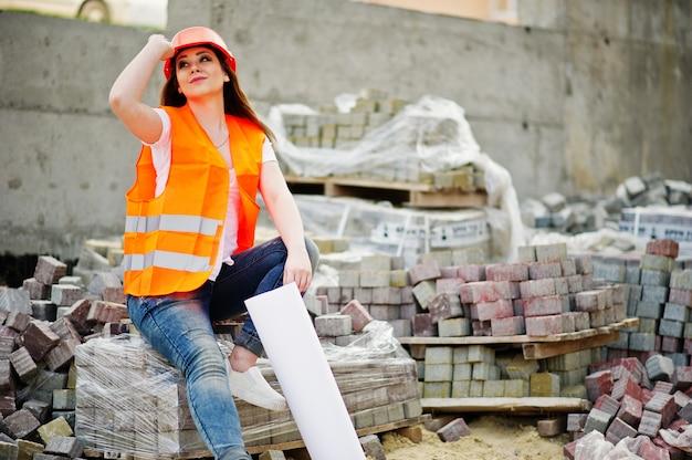 De vrouw van de ingenieursbouwer in eenvormig vest en oranje beschermende helm houdt het document van het bedrijfslay-outplan zitting op bestrating.