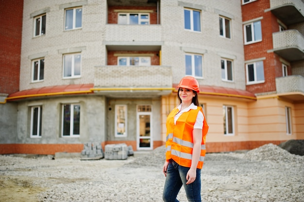 De vrouw van de ingenieursbouwer in eenvormig vest en oranje beschermende helm tegen nieuw gebouw