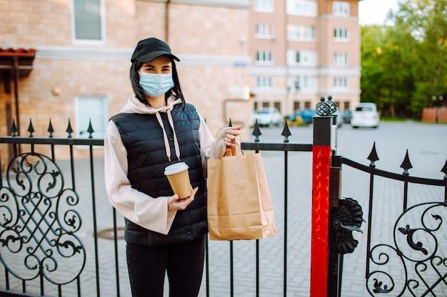 De vrouw van de levering in beschermend gezichtsmasker en handschoenen met een zak voedsel en koffie