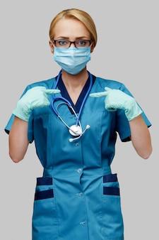De vrouw van de medische artsenverpleegster met stethoscoop die beschermend masker draagt en latexhandschoenen die bij zich tonen