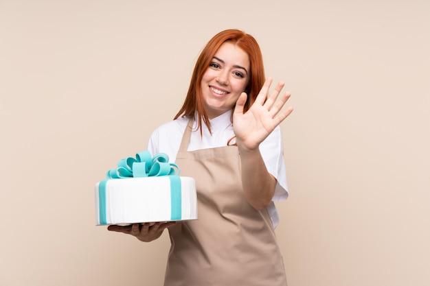 De vrouw van de roodharigetiener met een grote cake die met hand met gelukkige uitdrukking groeten
