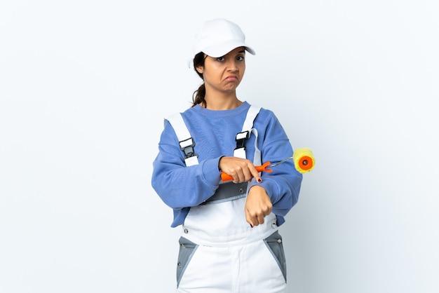 De vrouw van de schilder over geïsoleerde witte achtergrond die het gebaar maakt te laat te zijn
