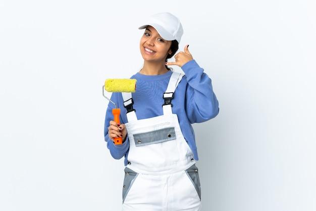 De vrouw van de schilder over geïsoleerde witte achtergrond die telefoongebaar maakt en naar voren wijst
