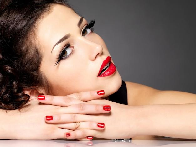 De vrouw van de schoonheidsmanier met rode spijkers, lippen en gouden oogmake-up - op zwarte muur