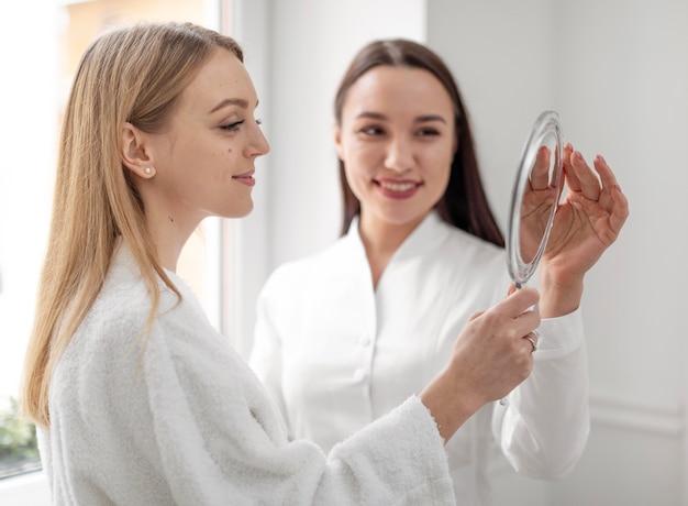 De vrouw van de schoonheidsspecialiste bij kliniek raadpleegt cliënt
