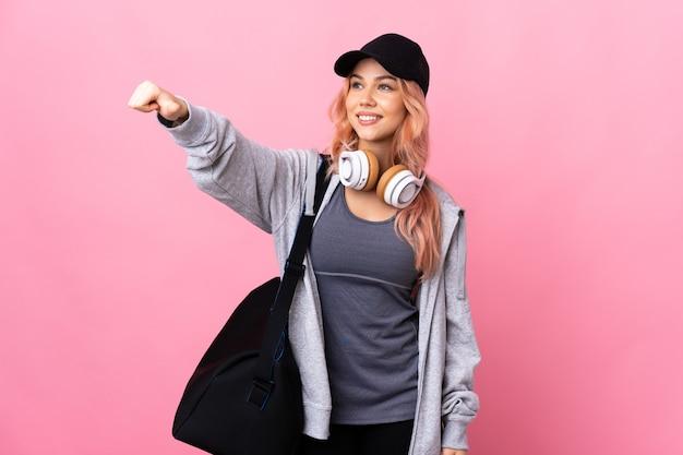 De vrouw van de tienersport met sporttas over geïsoleerde achtergrond die duimen op gebaar geeft