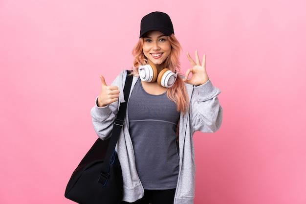 De vrouw van de tienersport met sporttas over geïsoleerde achtergrond die ok teken en duim op gebaar tonen