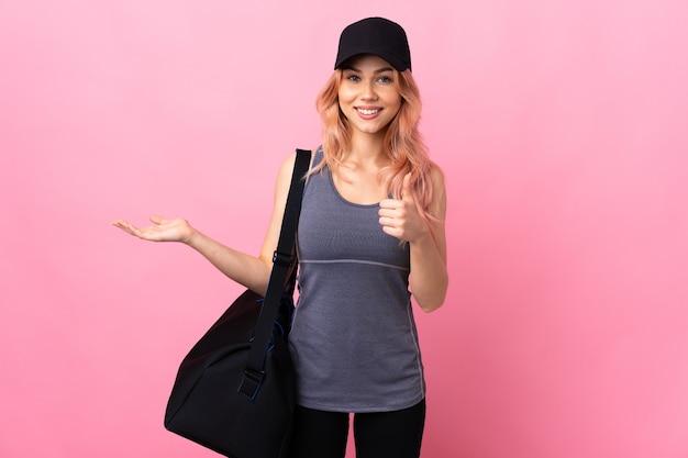 De vrouw van de tienersport met sporttas over geïsoleerde muur die copyspace denkbeeldig op de palm houdt om een advertentie en met omhoog duimen in te voegen