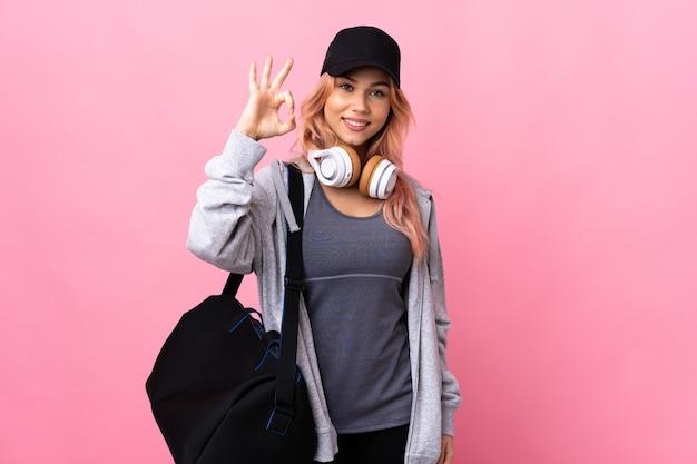 De vrouw van de tienersport met sporttas over geïsoleerde muur die ok teken met vingers tonen
