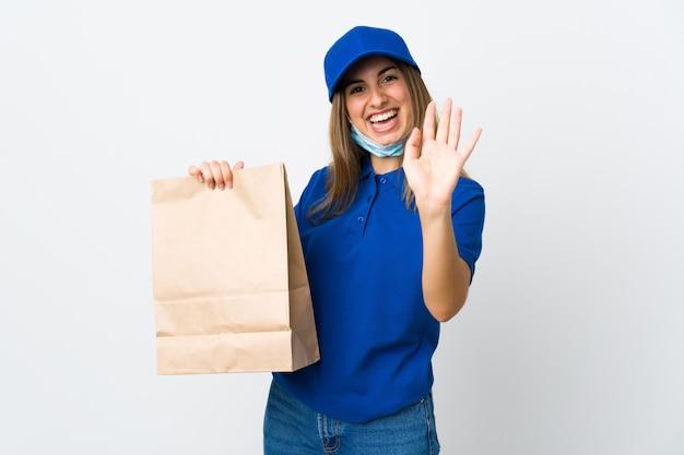 De vrouw van de voedsellevering en het beschermen tegen het coronavirus met een masker over geïsoleerde witte muur die met hand met gelukkige uitdrukking groeten