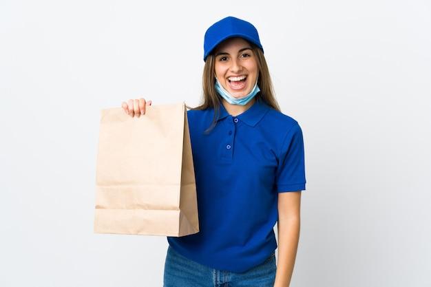 De vrouw van de voedsellevering en het beschermen tegen het coronavirus met een masker over geïsoleerde witte muur die veel glimlachen