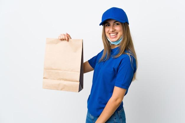 De vrouw van de voedsellevering over witte muur die veel glimlachen