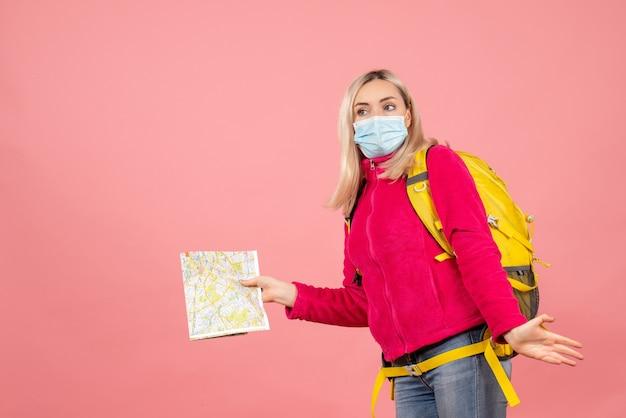 De vrouw van de vooraanzichtreiziger met gele rugzak die de medische kaart van de maskerholding dragen