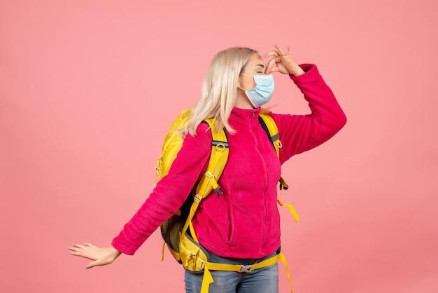 De vrouw van de vooraanzichtreiziger met gele rugzak die de neus van de maskerholding dragen