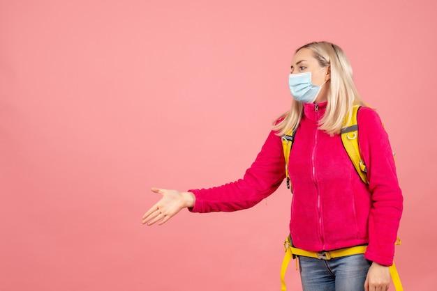 De vrouw van de vooraanzichtreiziger met gele rugzak die masker draagt dat hand geeft