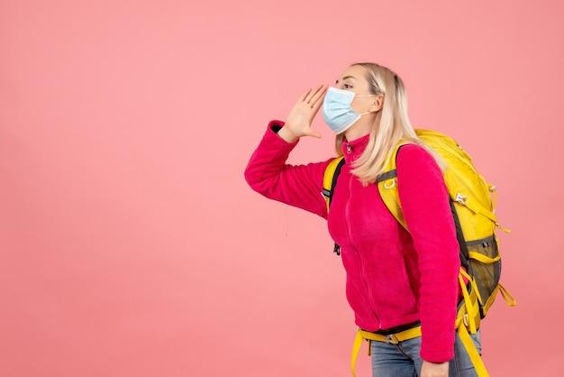 De vrouw van de vooraanzichtreiziger met gele rugzak die masker draagt dat iemand roept