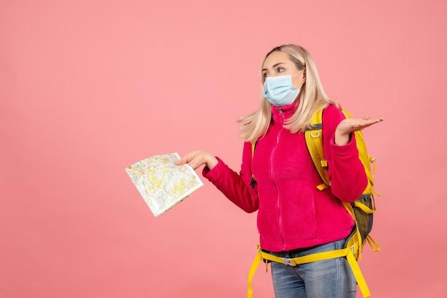 De vrouw van de vooraanzichtreiziger met gele rugzak die masker draagt dat kaart steunt