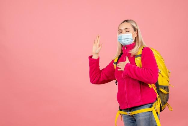 De vrouw van de vooraanzichtreiziger met gele rugzak die masker draagt dat met gesloten ogen belooft