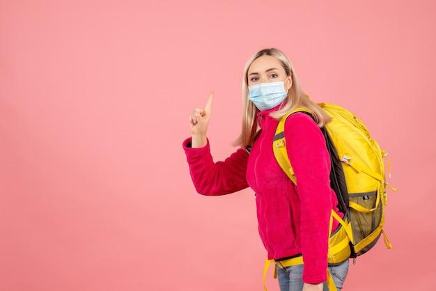 De vrouw van de vooraanzichtreiziger met gele rugzak die masker draagt dat omhoog wijst