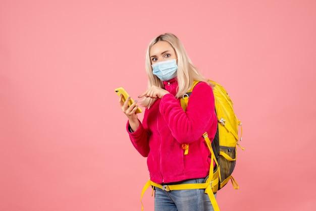 De vrouw van de vooraanzichtreiziger met gele rugzak die masker draagt dat op telefoon richt