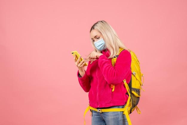 De vrouw van de vooraanzichtreiziger met gele rugzak die masker draagt die telefoon met behulp van